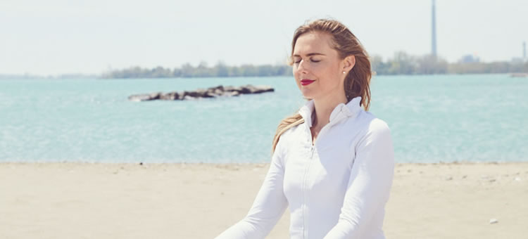 Nicole Campbell meditating on a beach